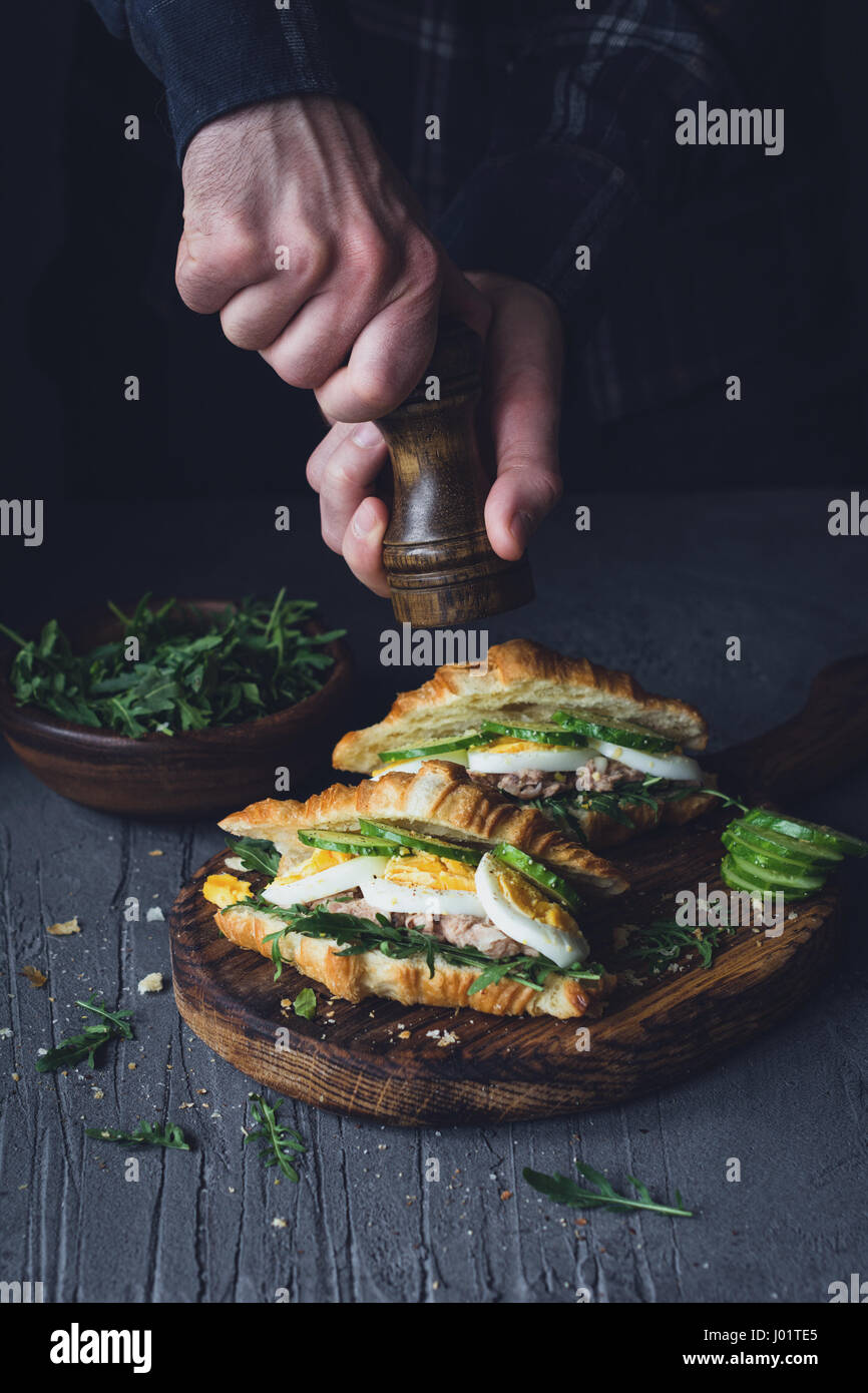 Hands peppering sandwiches with tuna salad. Selective focus, toned image - Stock Image