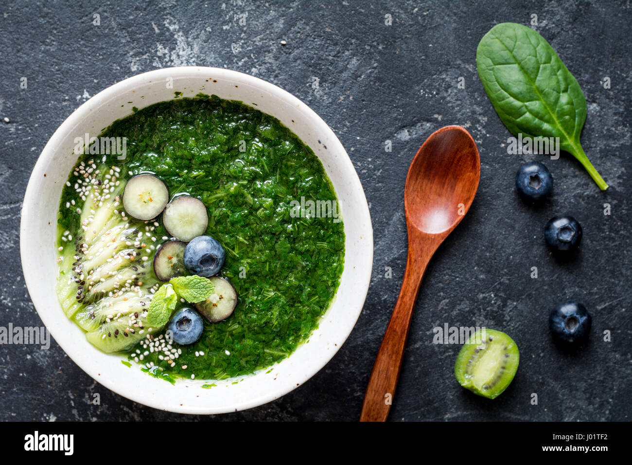 Green spinach and kale smoothie with chia seeds, kiwi and blueberries on slate background. Top view, closeup - Stock Image