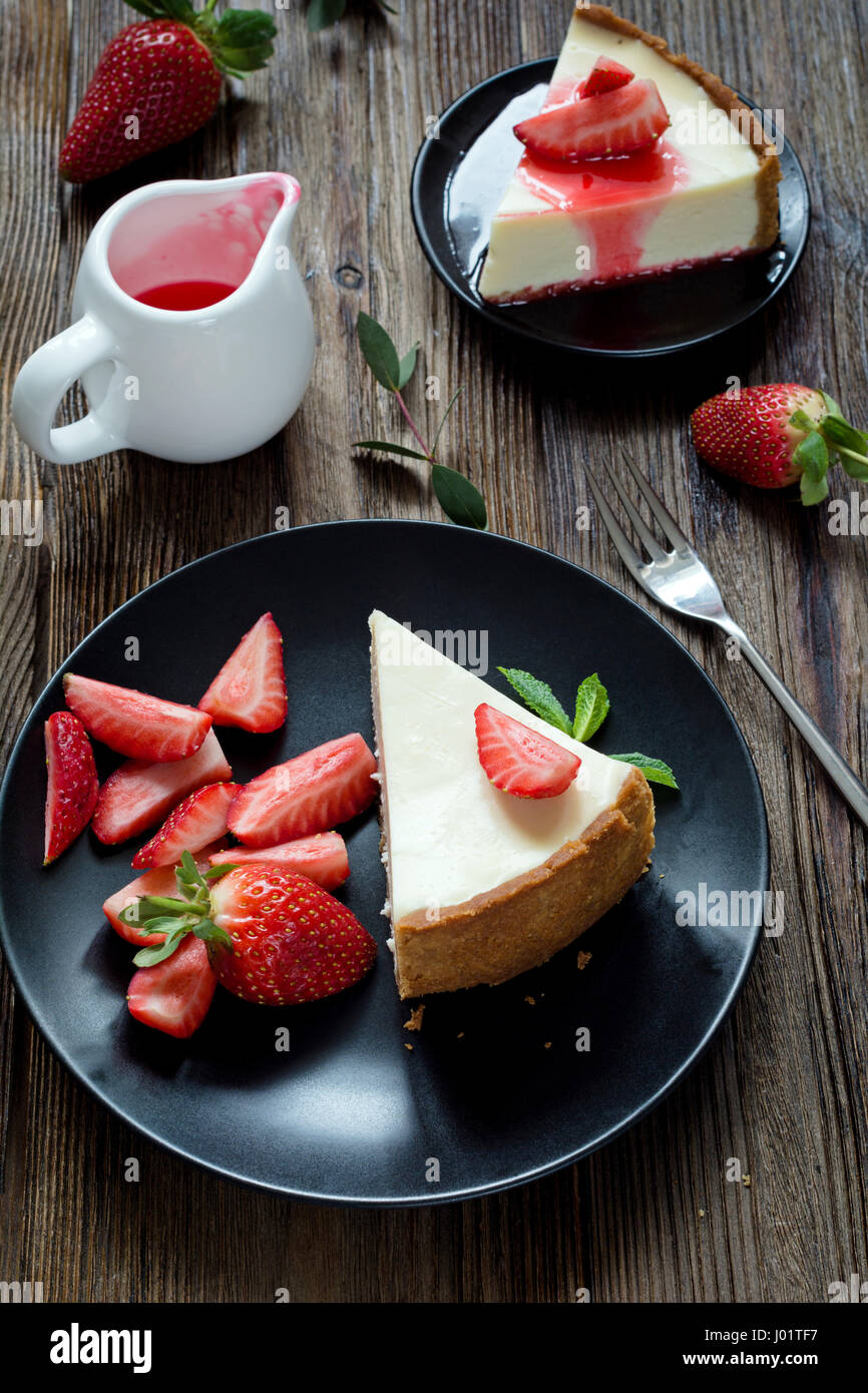 Strawberry cheesecake on black plate over rustic wooden background. Top view - Stock Image