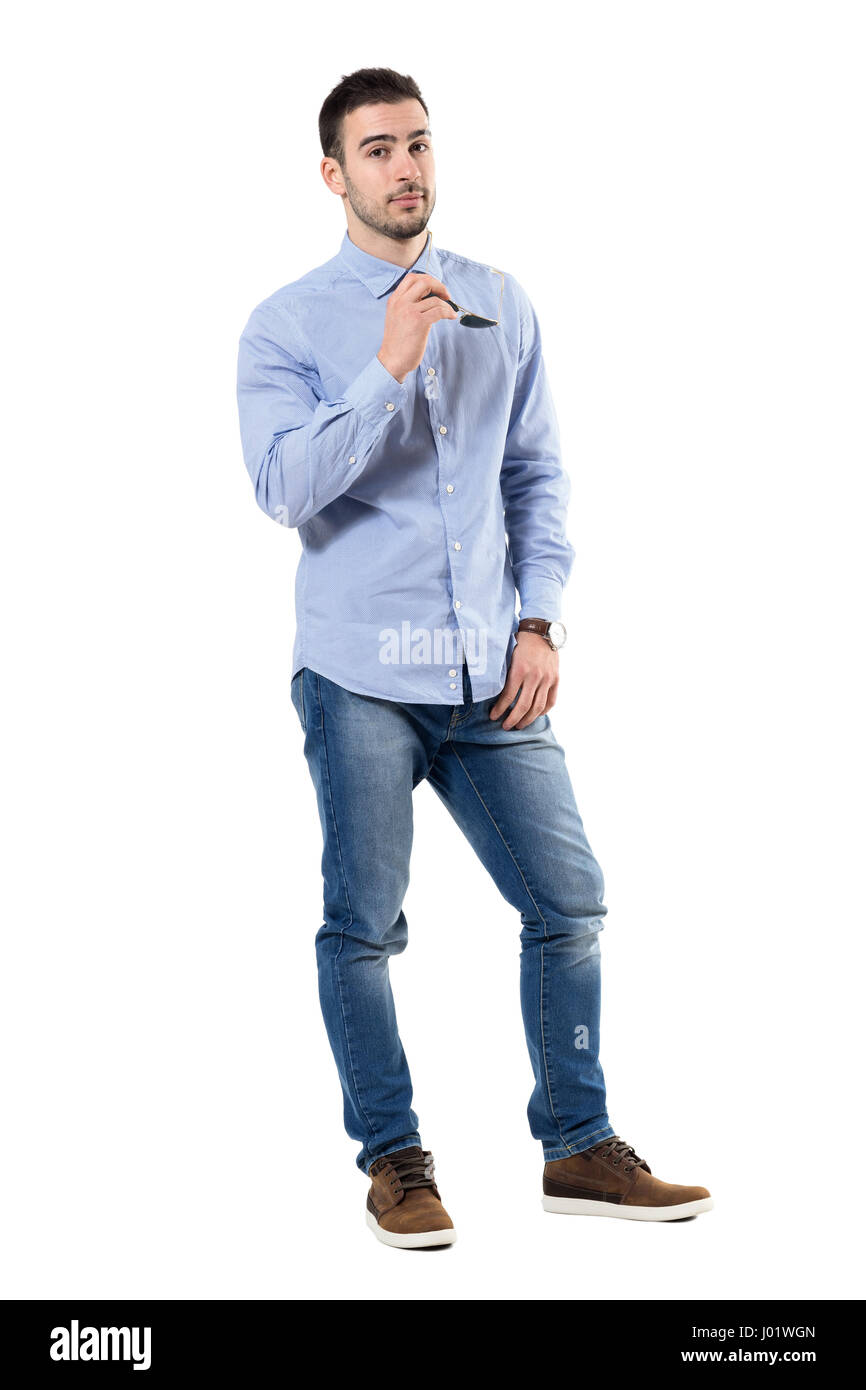 0ec3dd46fd Confident successful smart casual businessman holding sunglasses looking at  camera. Full body length portrait isolated over white background.