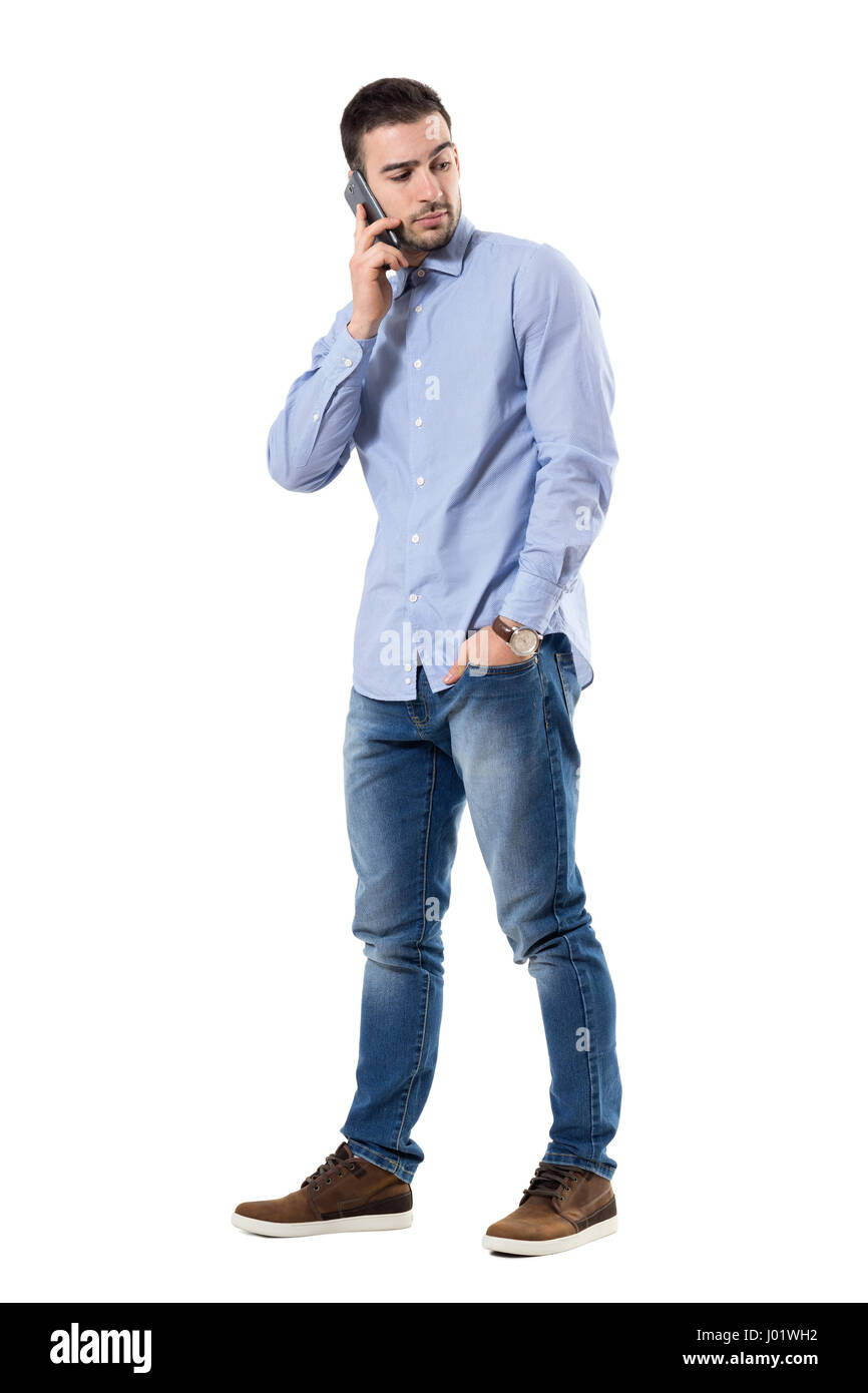 cf02762d0a0 Serious young skeptical businessman talking on the phone looking back. Full  body length portrait isolated