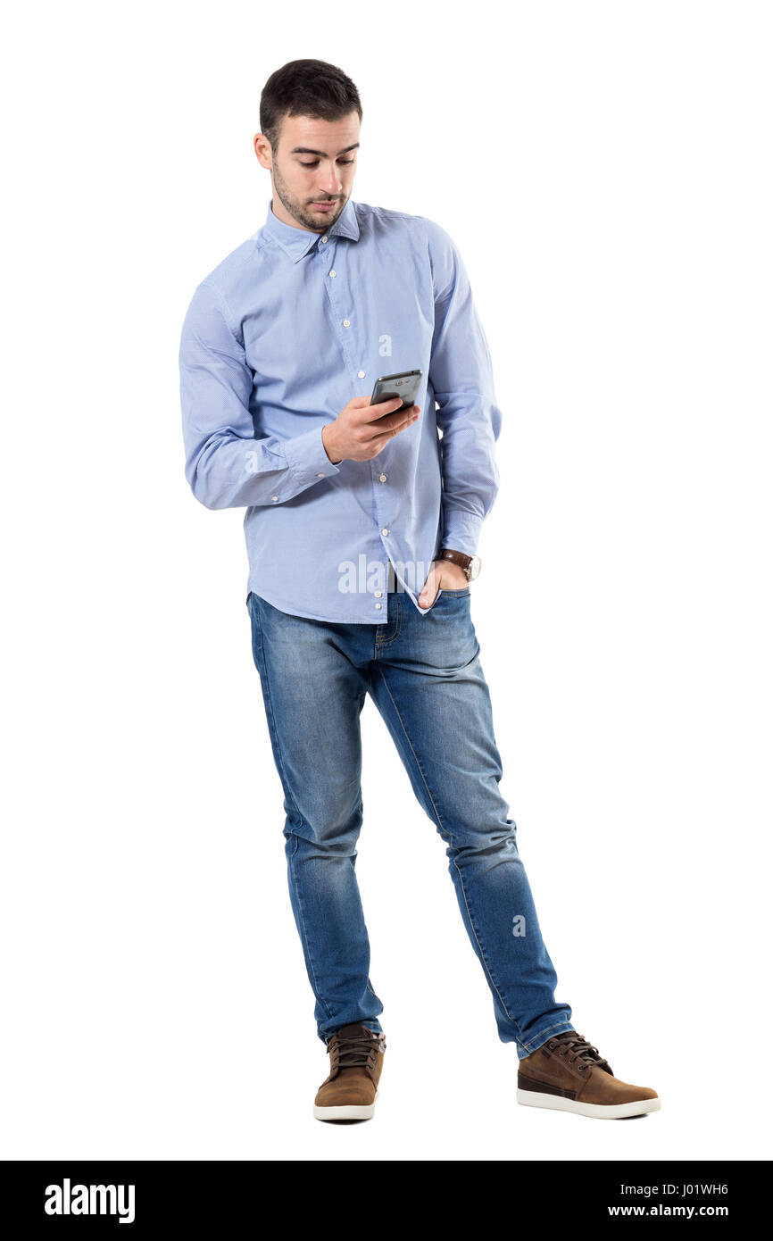 6e27ceeaad5 Relaxed young smart casual business man typing message on mobile phone. Full  body length portrait isolated over white background.