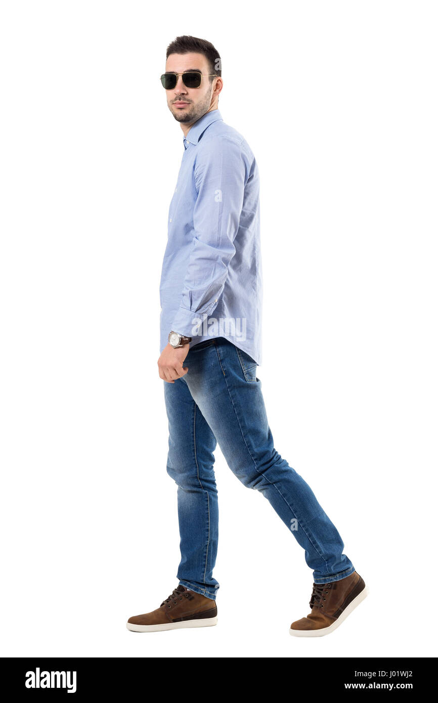 72df8f1ef3f Side view of young smart casual man wearing sunglasses walking and looking  at camera. Full