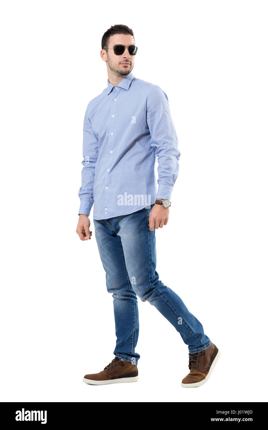 183abb21c3 Smart casual young business man wearing sunglasses walking looking back.  Full body length portrait isolated over white background.