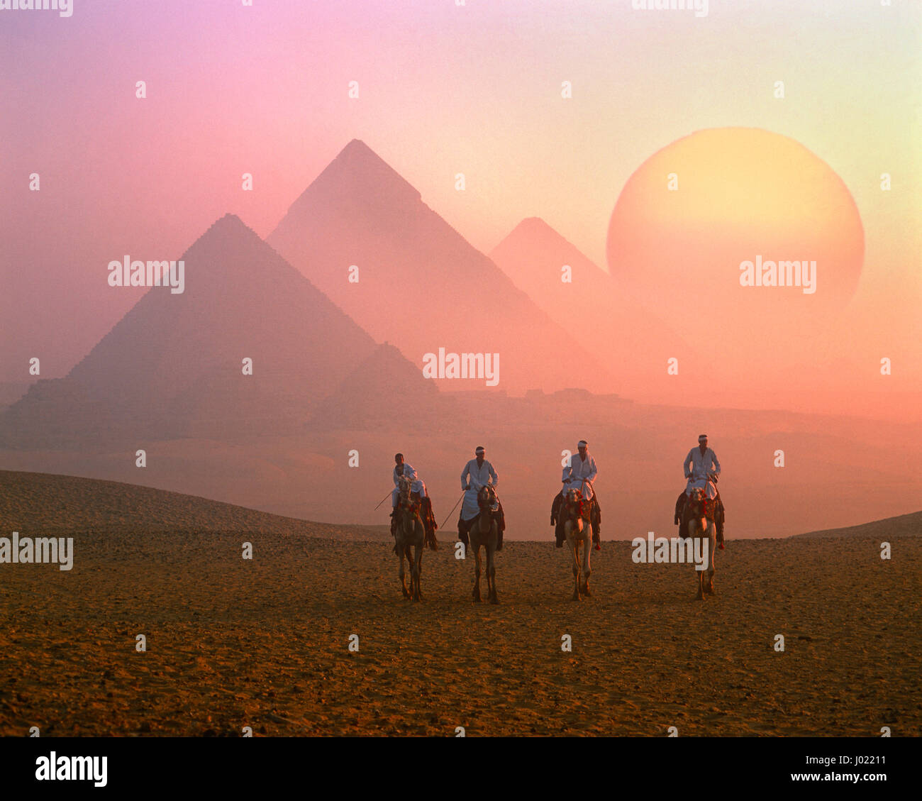 Four camel riders, the Pyramids and the rising sun, Giza, Cairo, Egypt - Stock Image