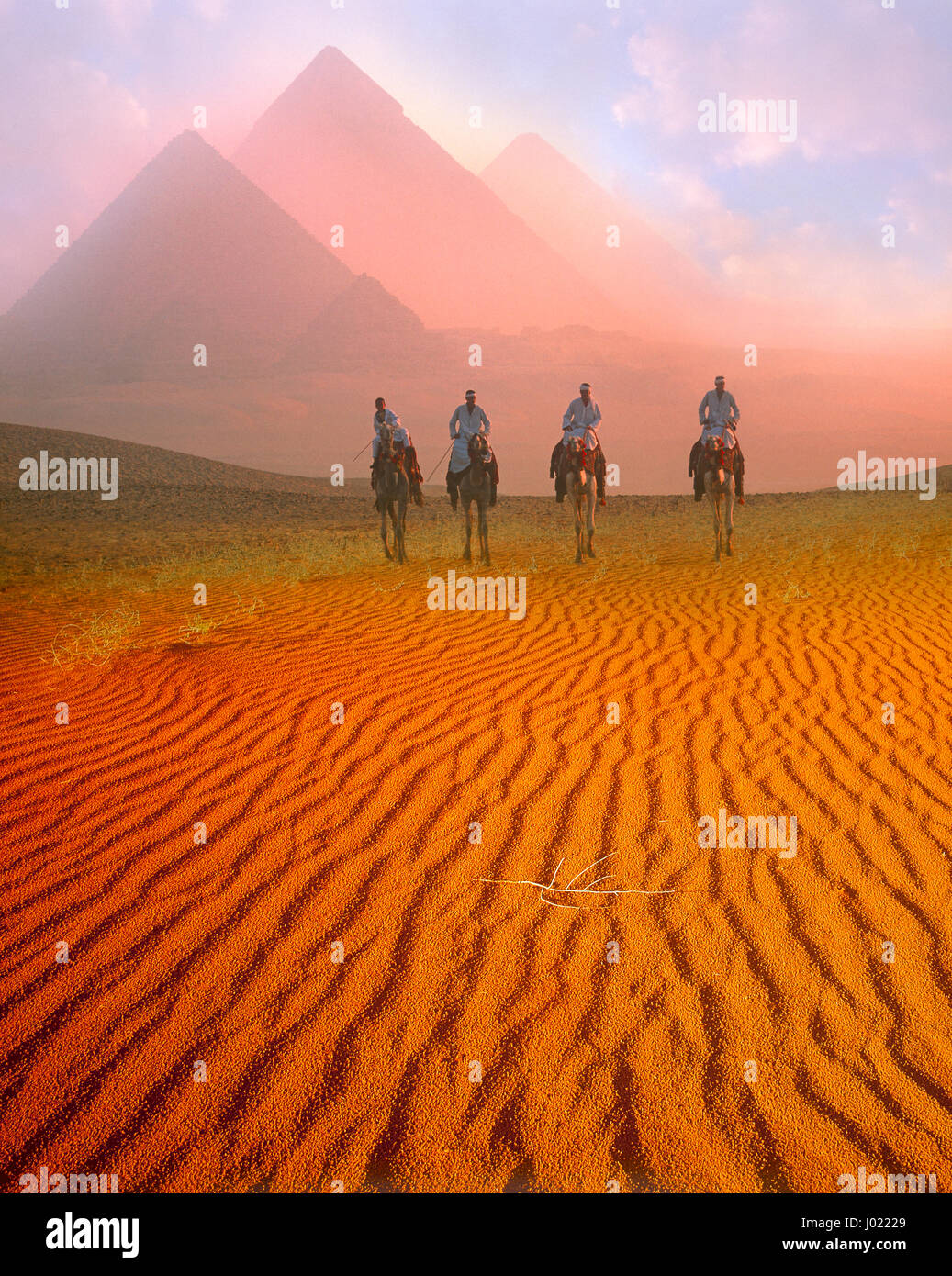 Pyramids and camelriders at dawn, Giza, Cairo, Egypt - Stock Image