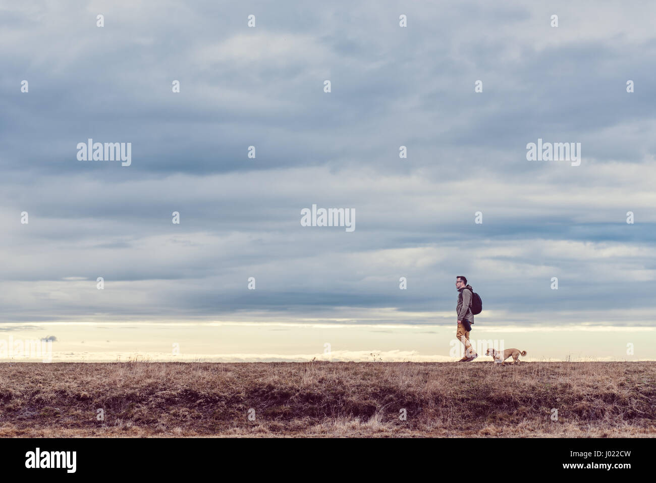 Hiker and dog walking in grassland on a cloudy day Stock Photo
