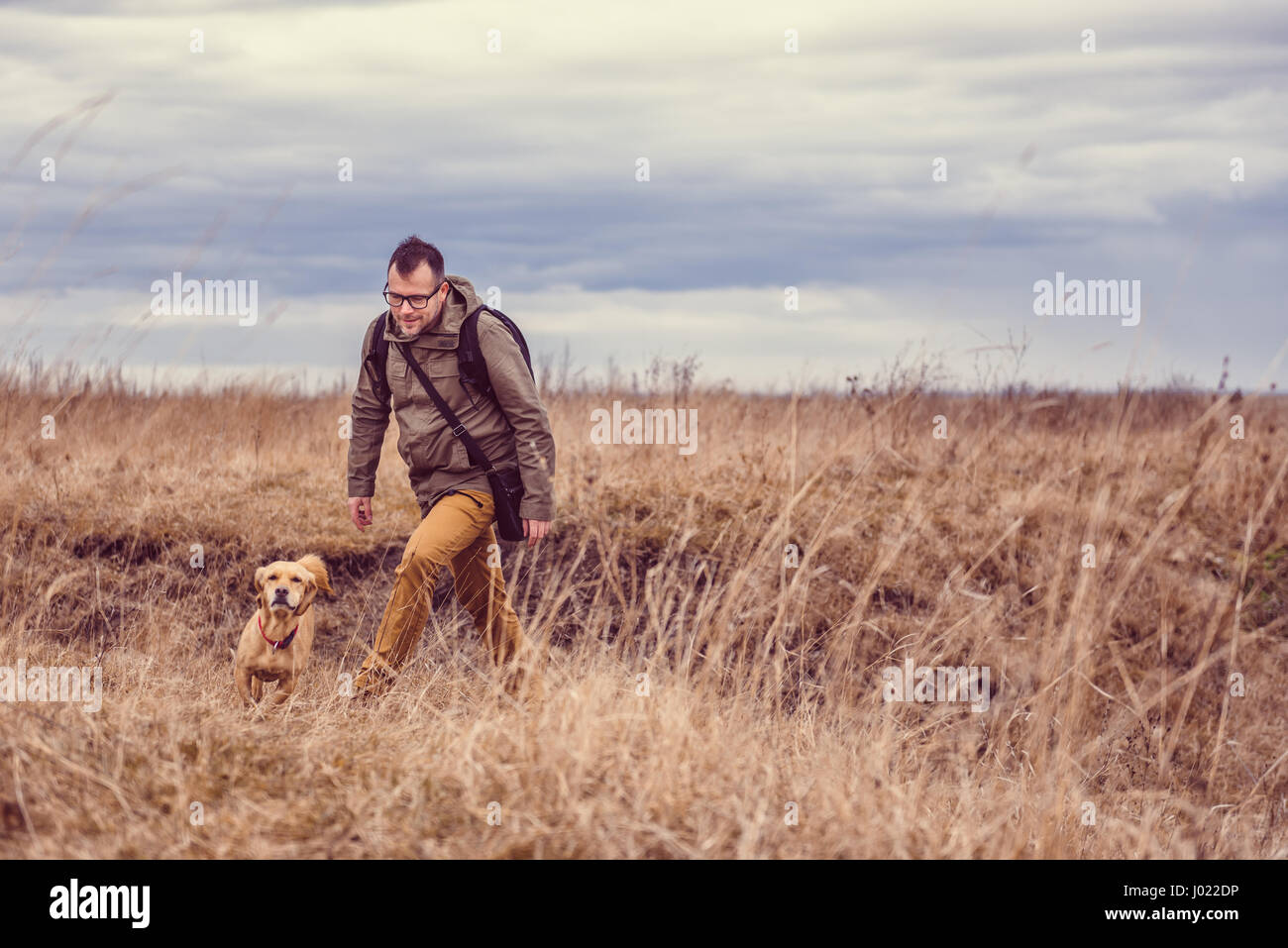 Hiker and small yellow dog walking in grassland on a cloudy day - Stock Image