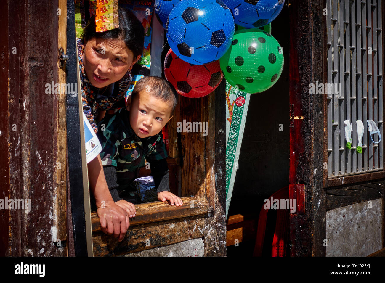 A mother and son look out from the window of their doma shop in Thimphu Bhutan - Stock Image