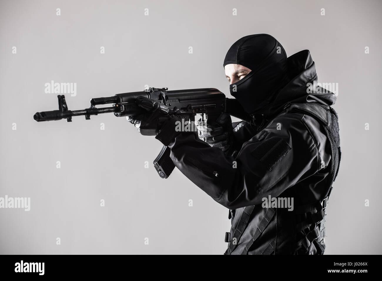 Terrorist aim with gun on isolated grey background - Stock Image