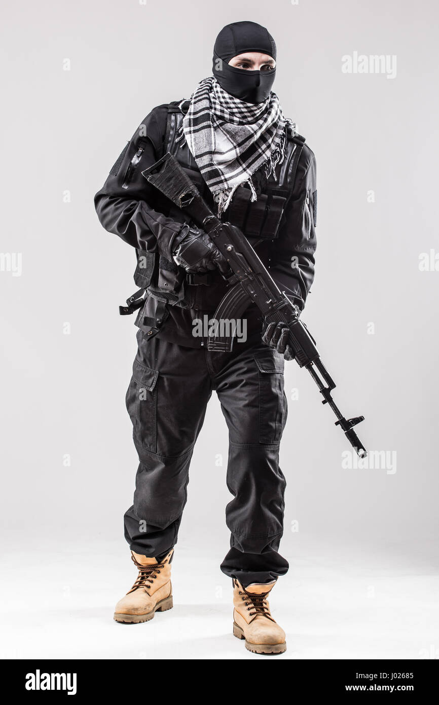 Terrorism concept: Terrorist holding a machine gun in his hands isolated over white - Stock Image