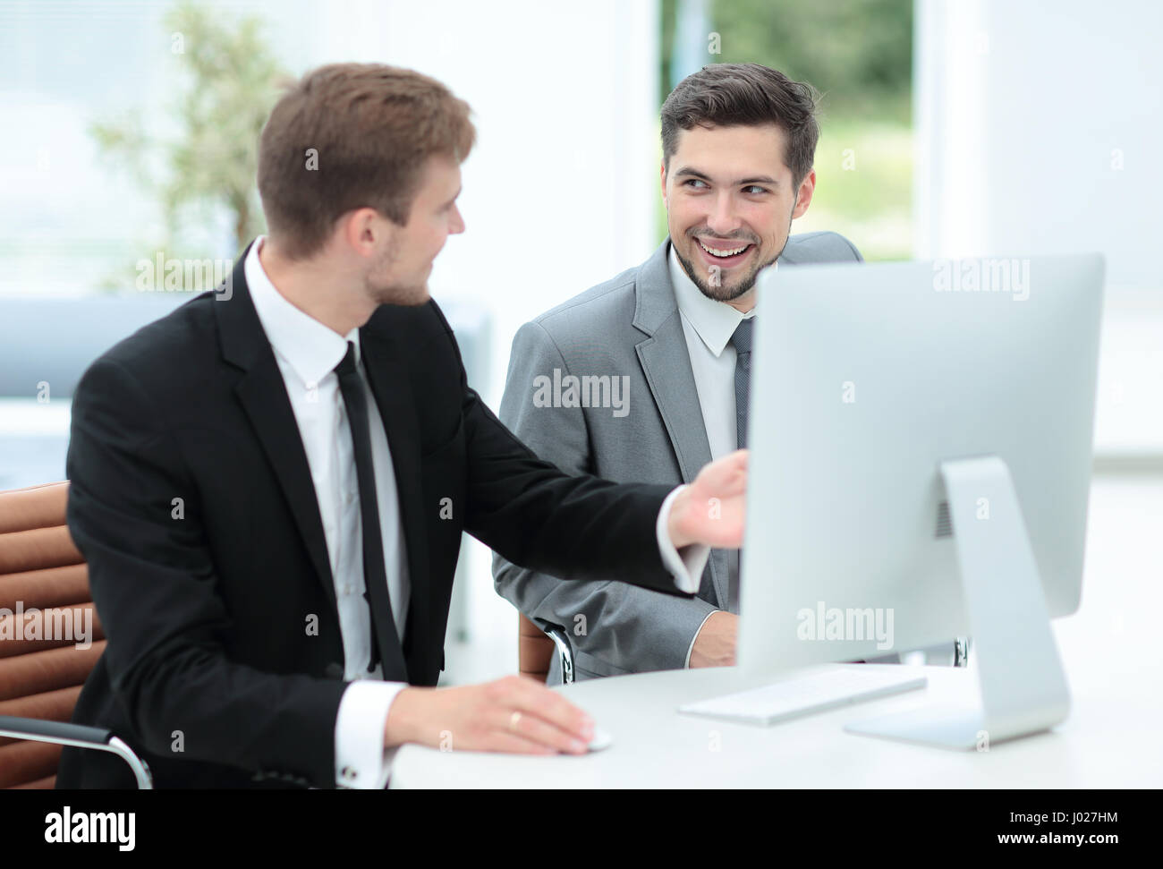 Two successful business men discussing documents in a modern off - Stock Image