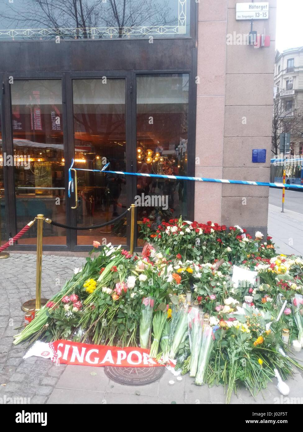 A stack of flowers pilledup in the evacuated Hotorget street in central Stockholm during police investigations in - Stock Image