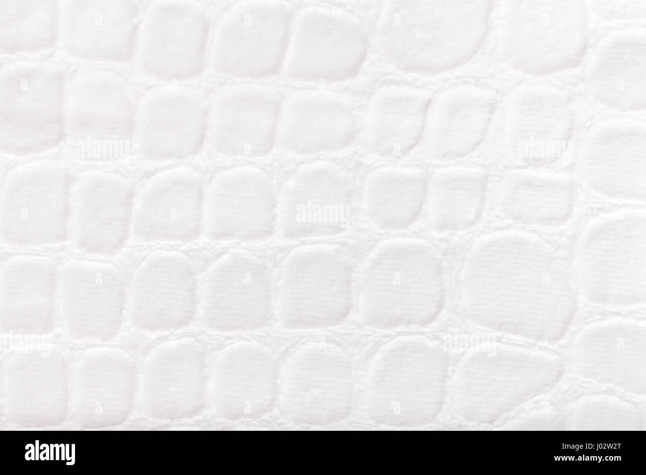White background from a soft upholstery textile material, closeup. Fabric with pattern imitating crocodile skin.. - Stock Image