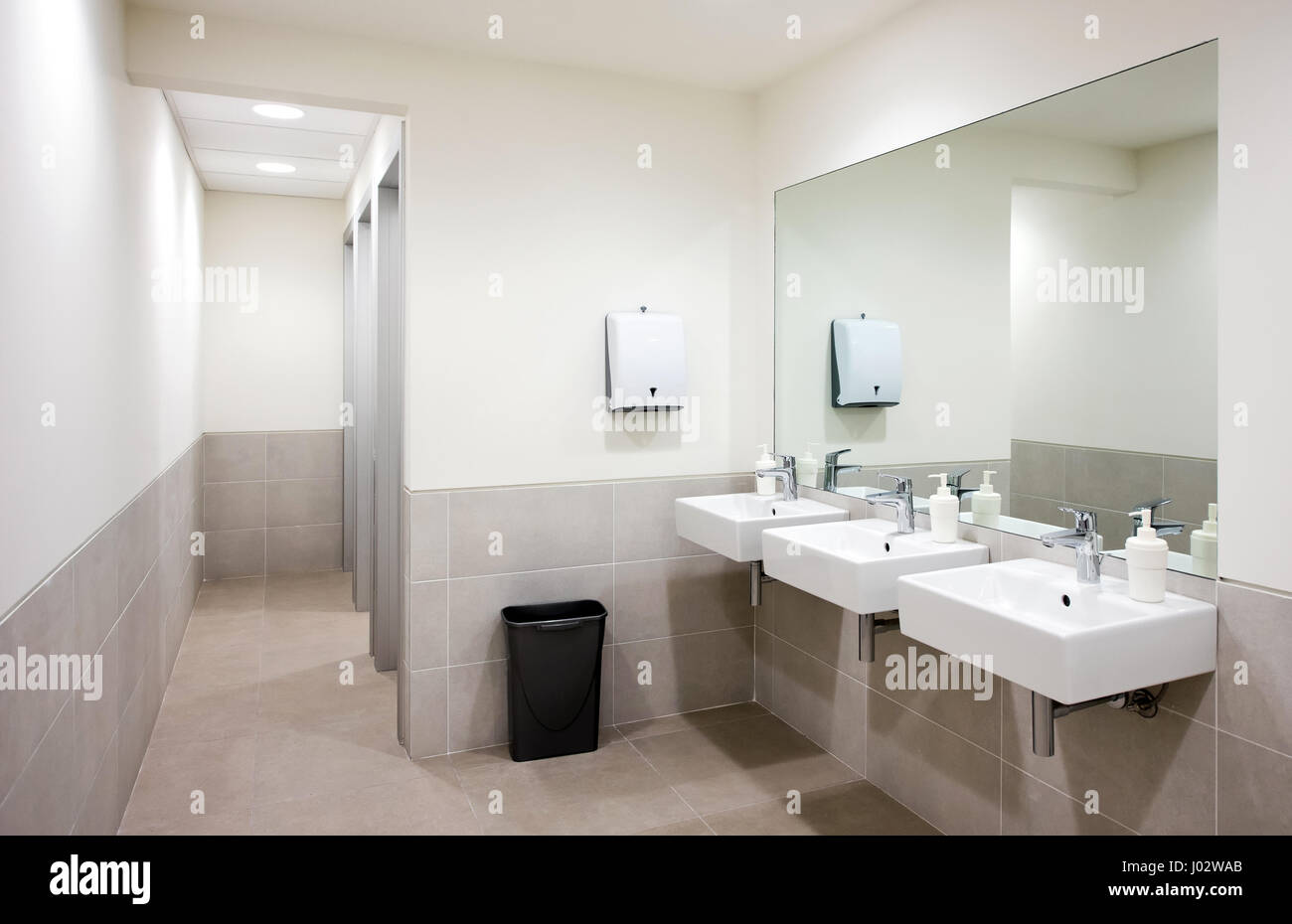 Empty public bathroom with white sinks and wide wall mirror, air ...