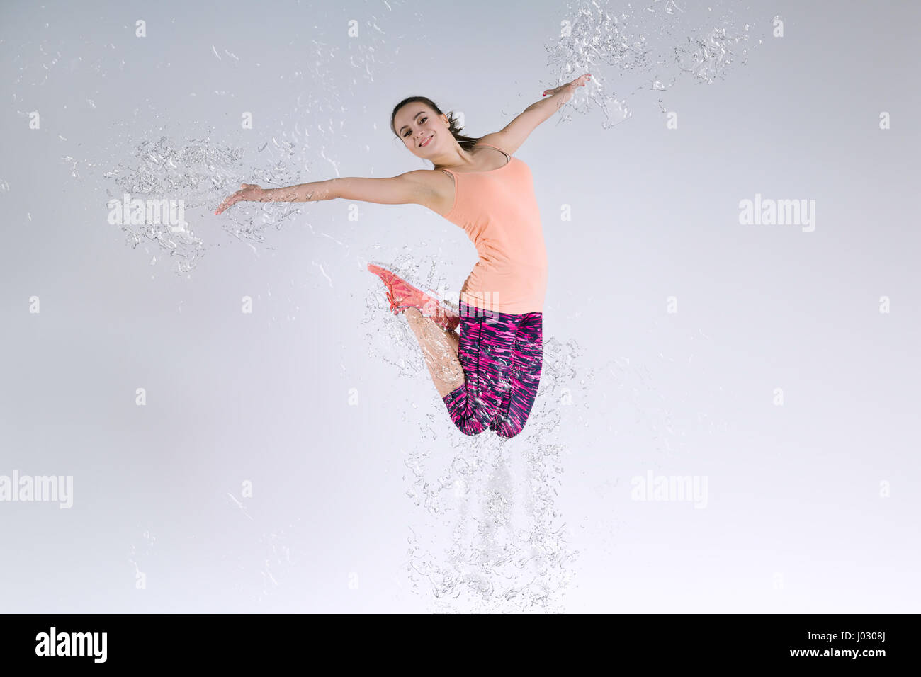 Woman Jumping In The Studio And Splashing Water