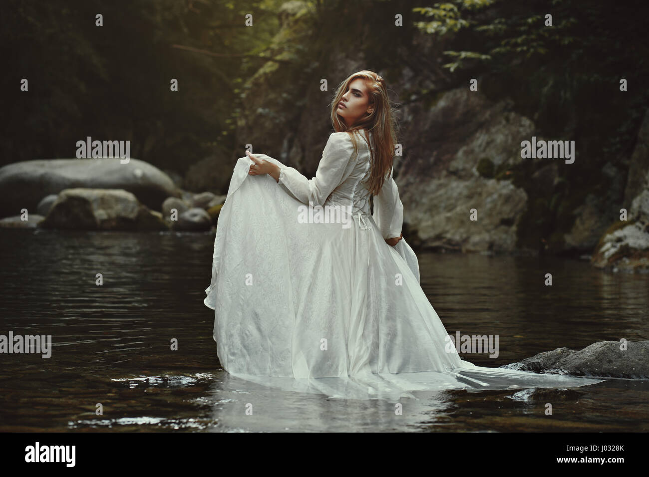 Beautiful ethereal woman in mystical waters. Fantasy pond - Stock Image