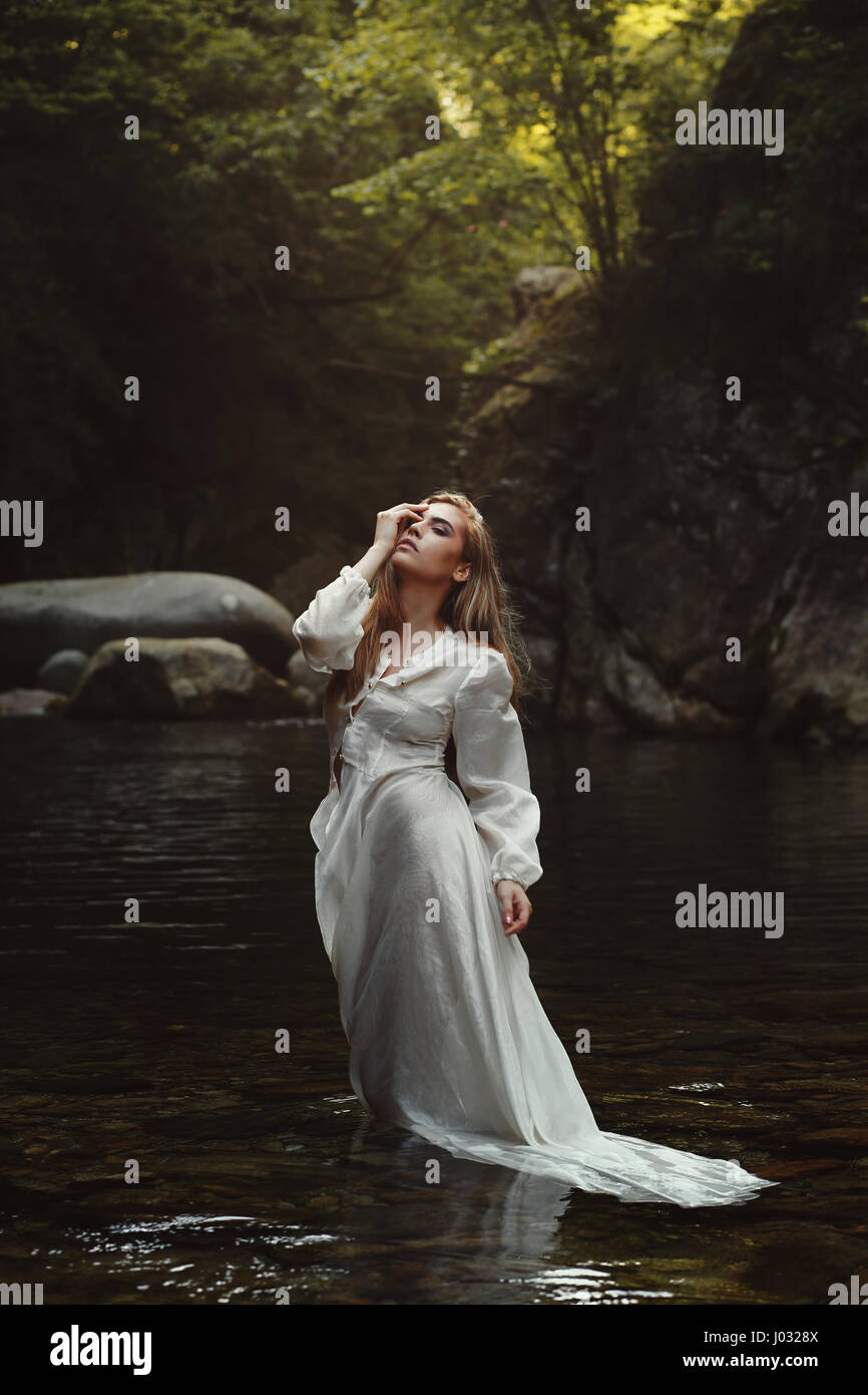 Young forest maiden in mystical waters. Dark woods Stock Photo