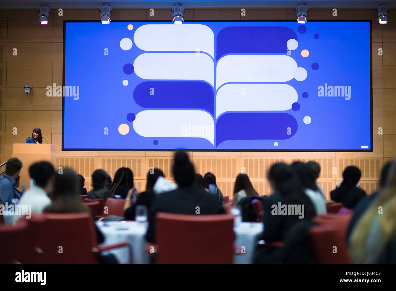 A large presentation screen facing an audience during an event - Stock Image