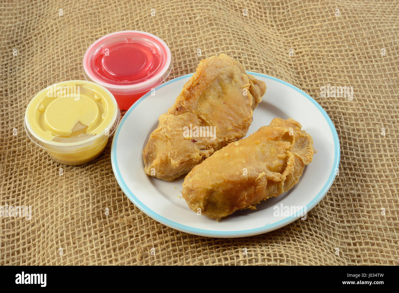 Fried chicken tenderloin appetizer with mustard and sweet and sour sauce - Stock Image