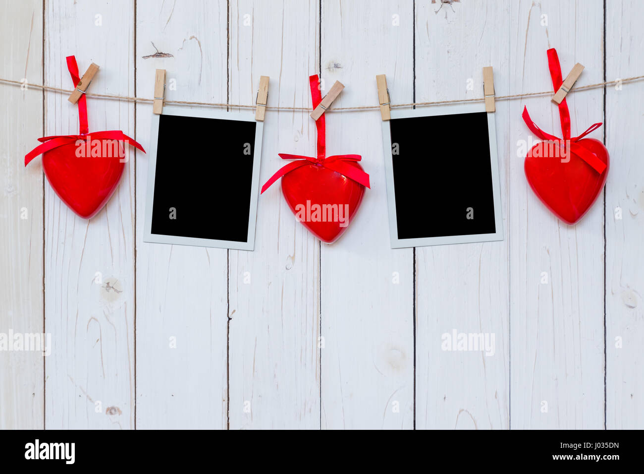 Photo frame blank and red heart hanging on white wood background ...