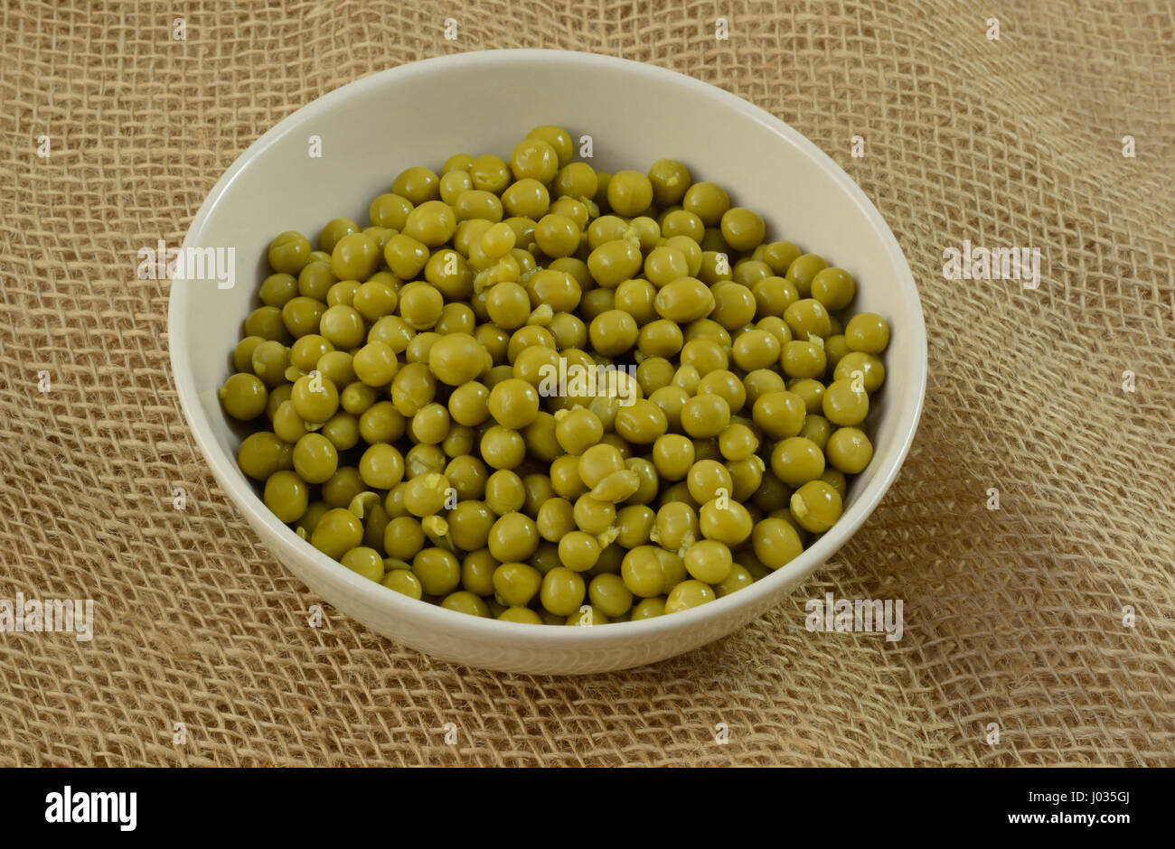 Canned low salt sweet peas in white bowl on burlap - Stock Image