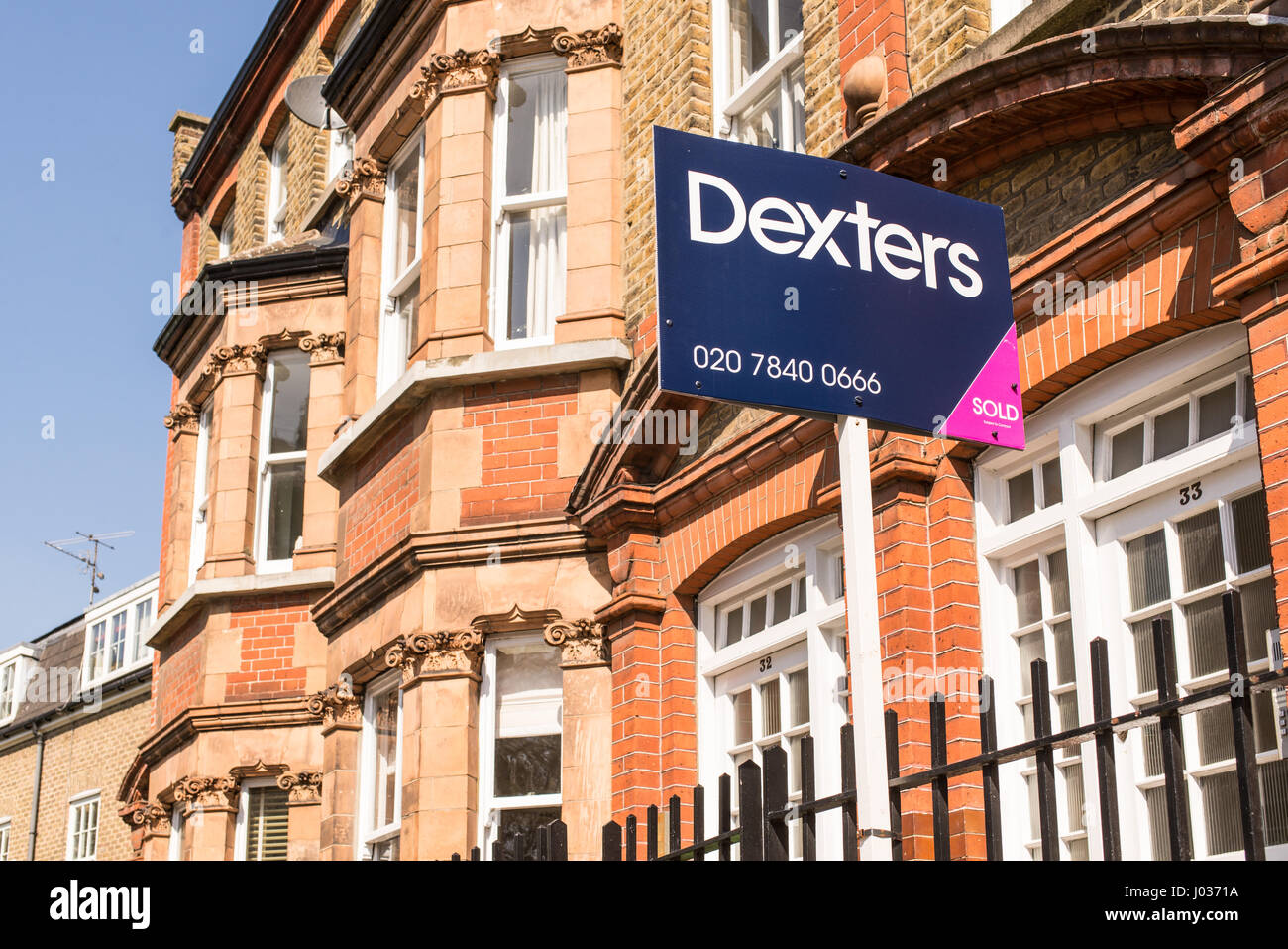 London, England, UK - April 2017: Estate agent sign outside a row of Victorian terraced houses in London, England, - Stock Image