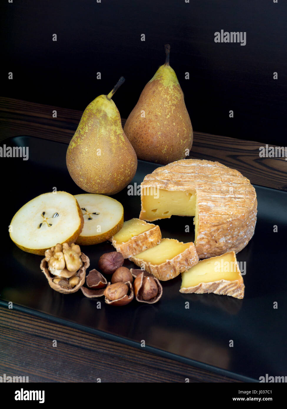 Soft washed-rind cheese, walnut, hazelnuts and pears on the black plate - Stock Image