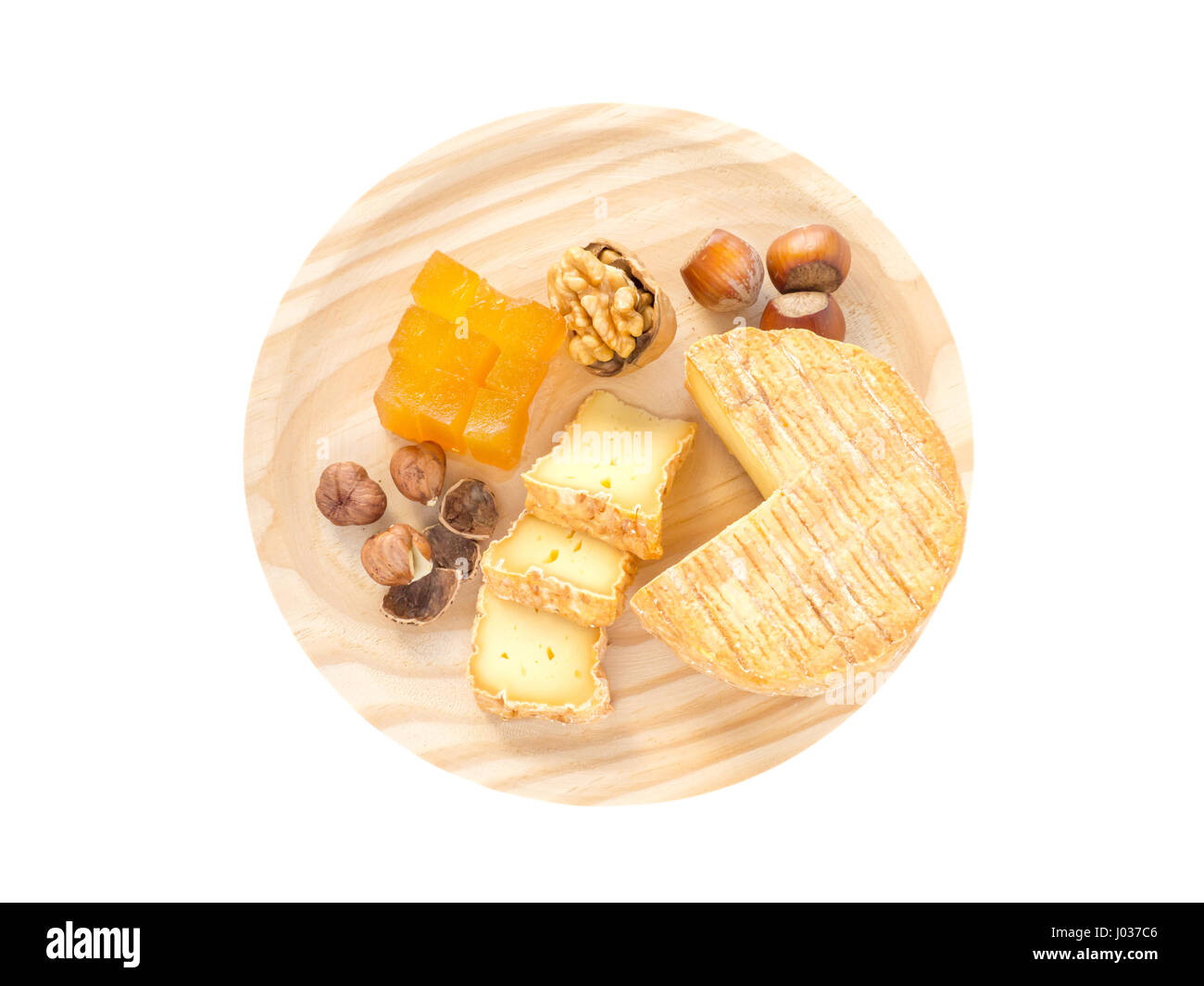 Soft washed-rind cheese, hazelnuts, walnut and marmalade on the textured wooden board top view isolated on white - Stock Image