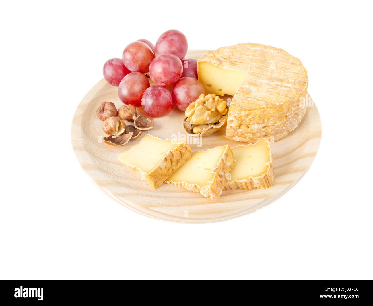 Soft washed-rind cheese, hazelnuts, walnut and red grape on the textured wooden board isolated on white - Stock Image