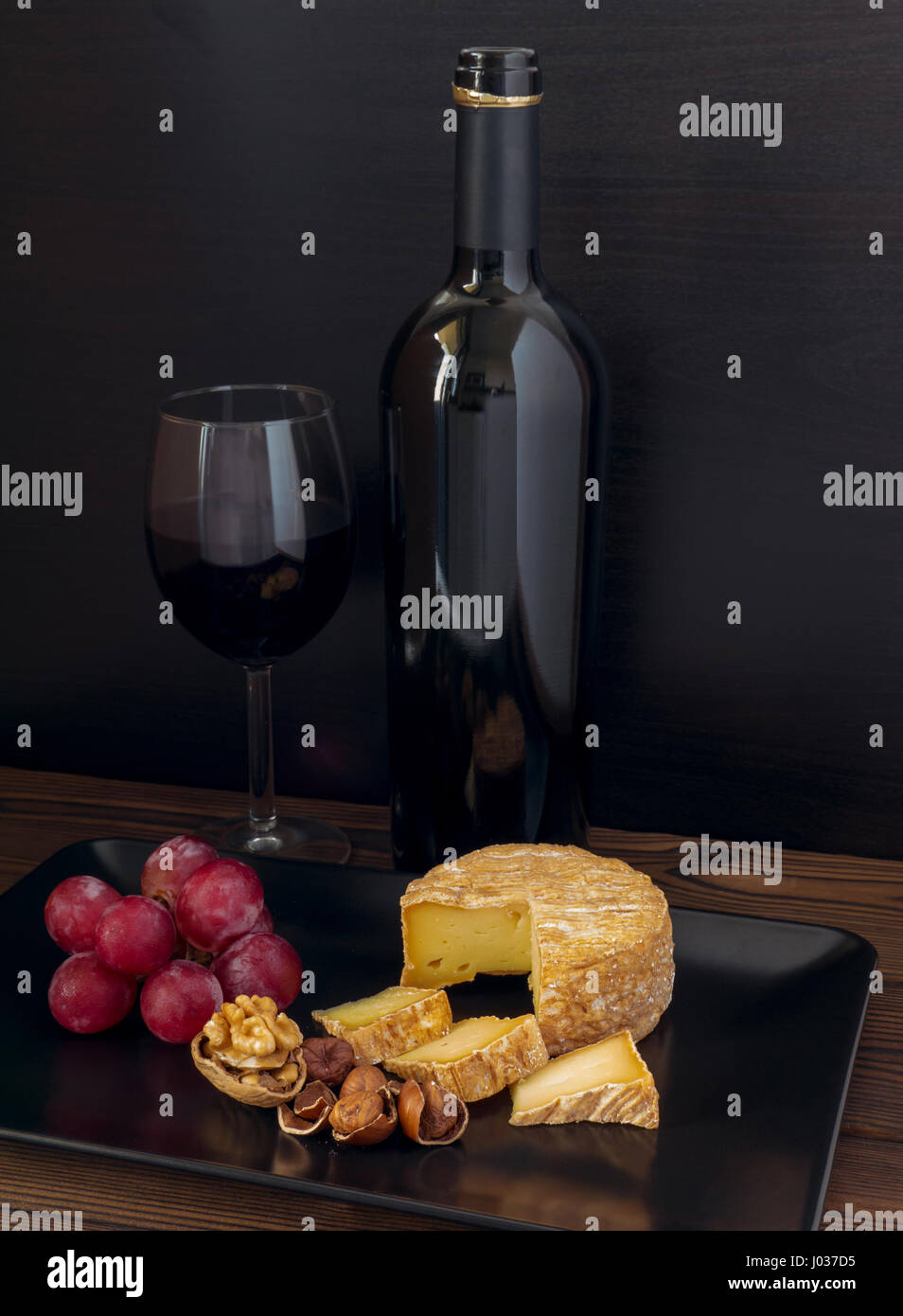 Soft washed-rind cheese, hazelnuts, walnut, red grape and wine in the glass and bottle - Stock Image