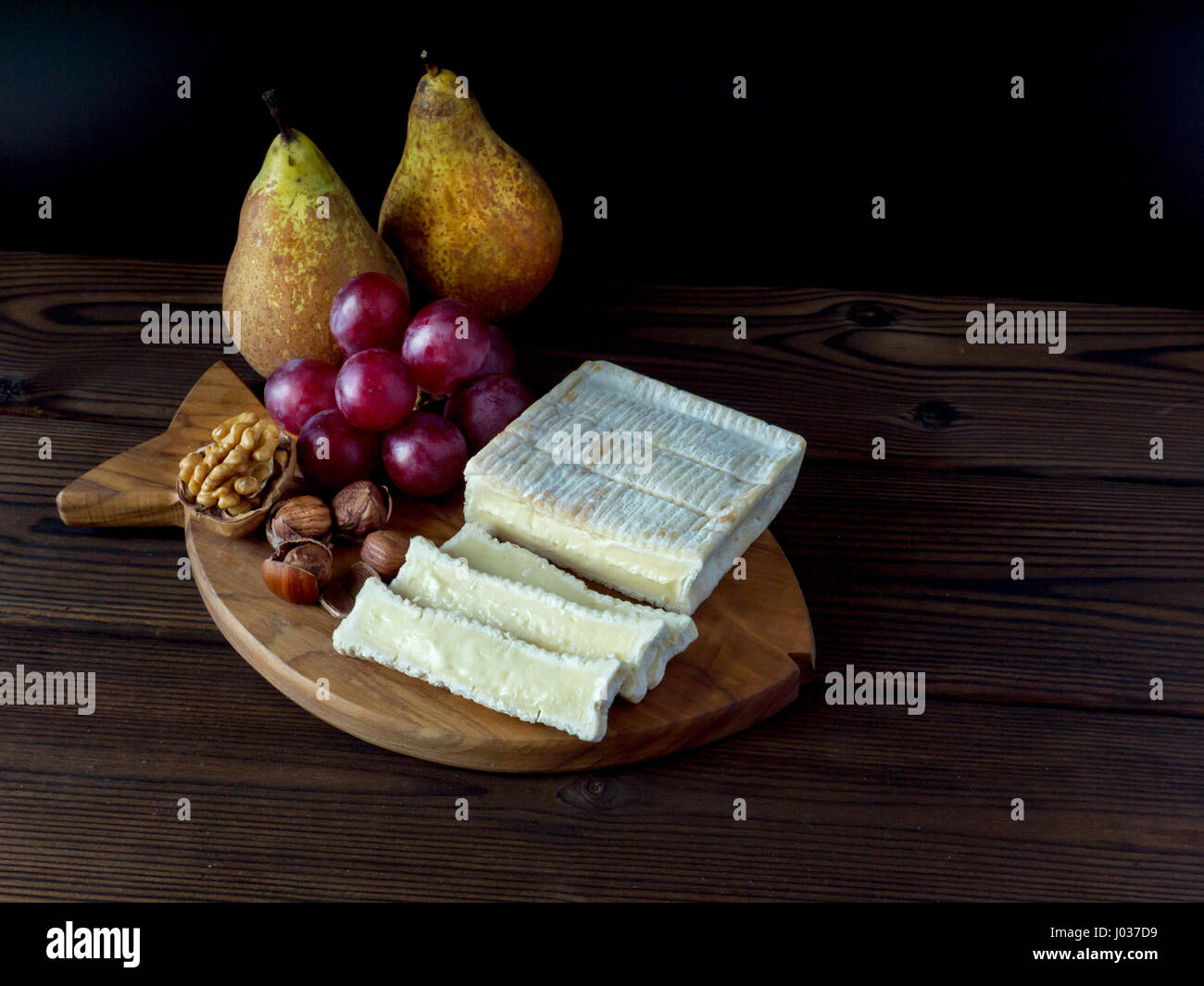 Brick shaped cheese with white mold, hazelnuts, walnut, red grape and pears on the textured wooden board - Stock Image