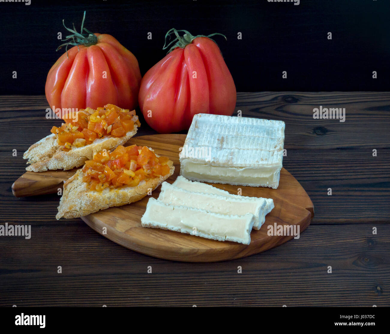 Brick shaped white mold cheese, ripe tomatoes and toasts on the textured wooden board - Stock Image