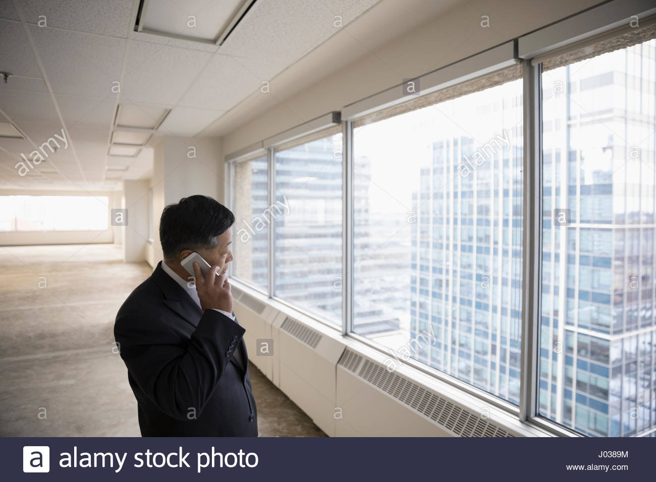 Businessman talking on cell phone in empty highrise office - Stock Image