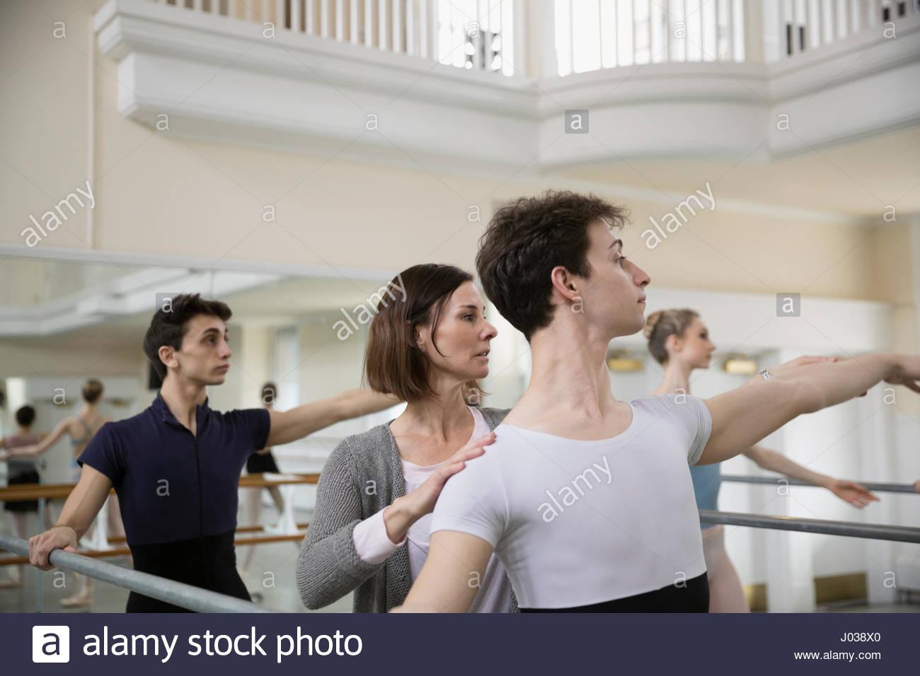 Instructor adjusting arms of male ballet dancer practicing in dance studio - Stock Image