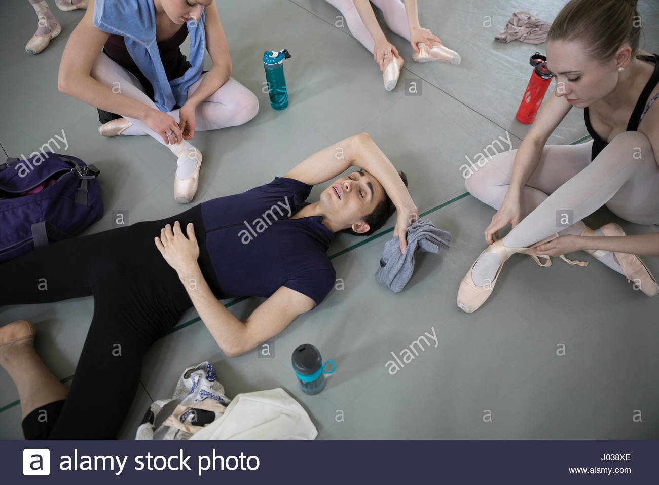 Tired male ballet dancer resting on floor in dance studio Stock Photo