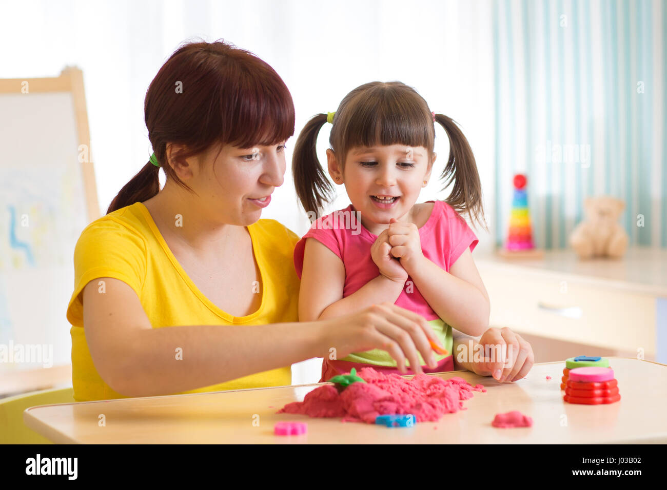 Cute child girl and mother playing with kinetic sand at home - Stock Image