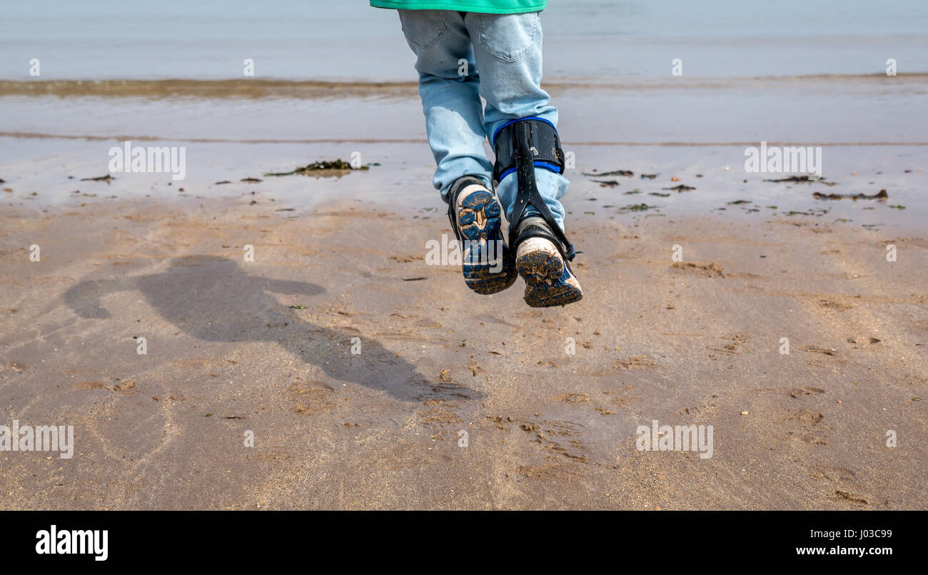 Young boy with right hemiplegia jumping on beach with shadow,  showing movement achieved by wearing carbon fibre - Stock Image