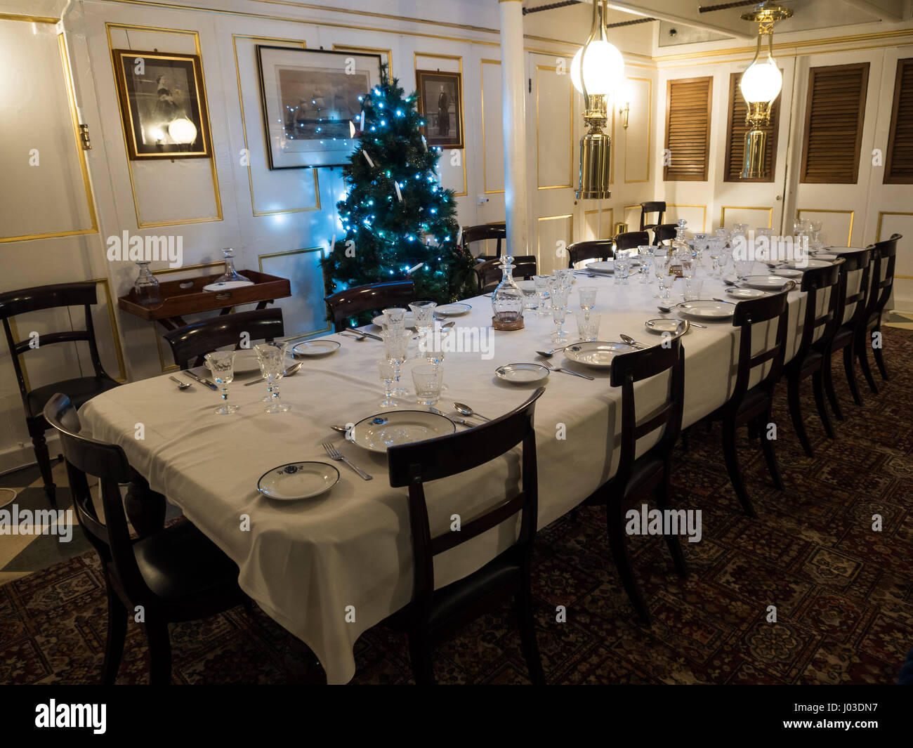 Officers table inside the Victorian age warship, HMS warrior at Portsmouth Dockyard - Stock Image