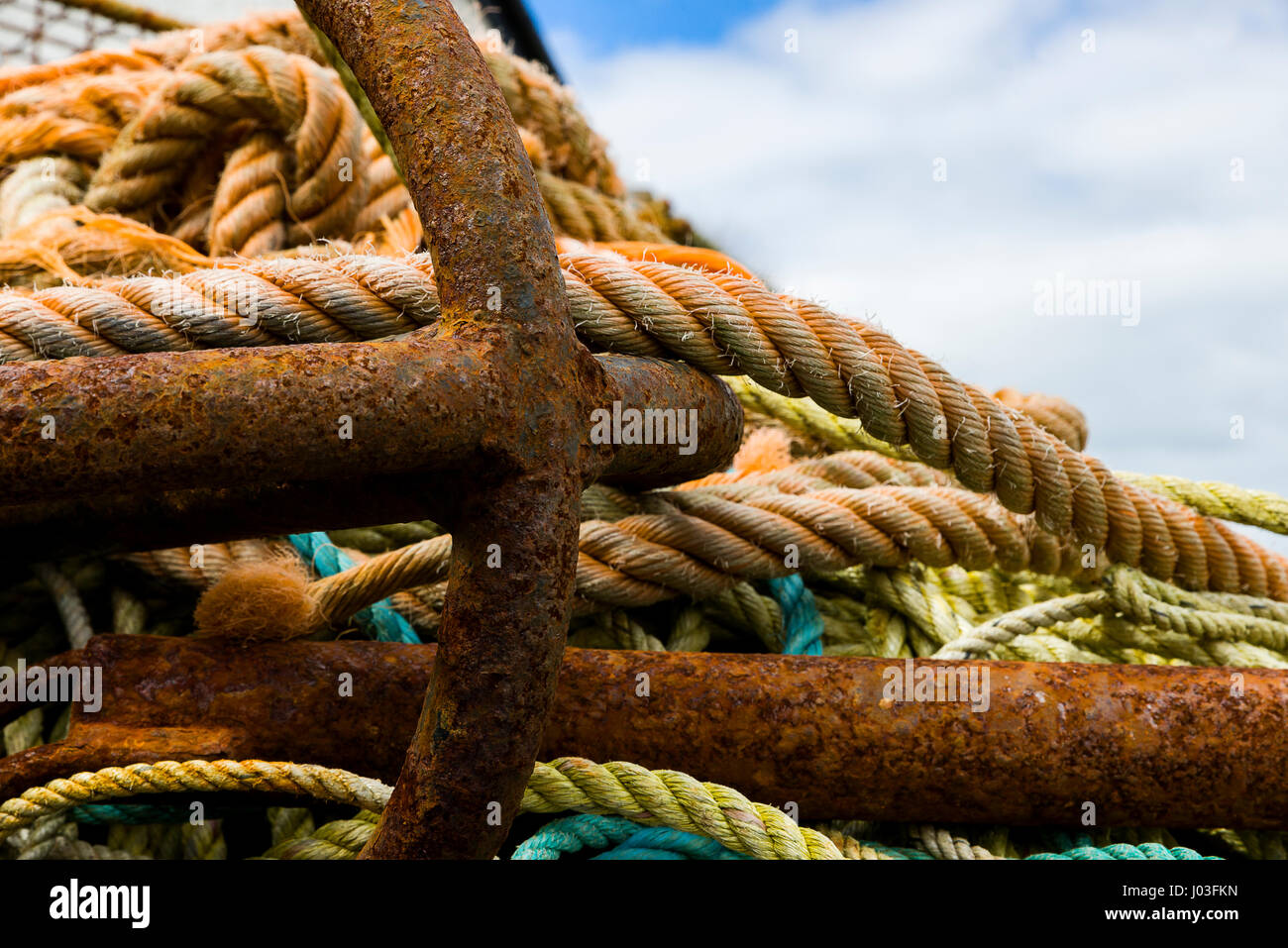 Various colourings of fishing rope and an industrial strength anchor wrapped together on the harbour edge at Mevagissey - Stock Image