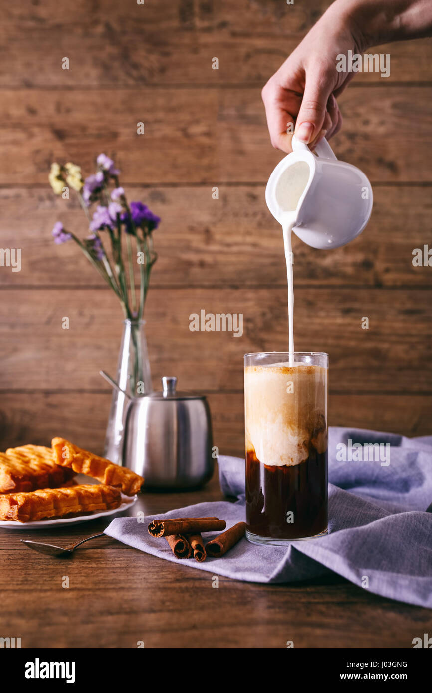 Women's hand with creamer pouring milk in glass with coffee. Cinnamon sticks, homemade cookies and bunch of - Stock Image