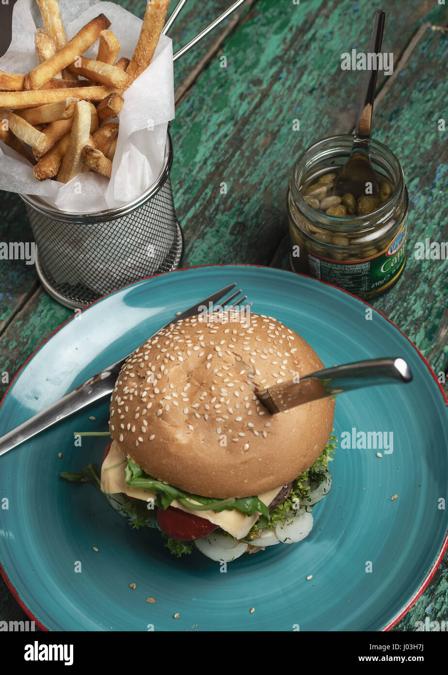 Cheese burger with french fries and capers on green grunge background - Stock Image