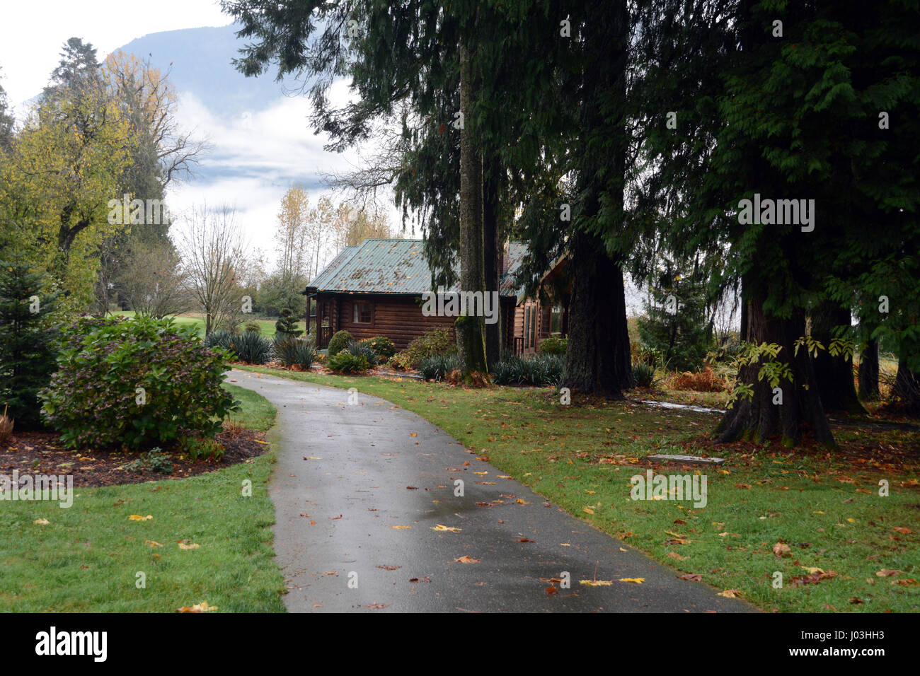 A luxurious log cabin on a manicured estate at the edge of the forest near the town of Harrison Mills, British Columbia, - Stock Image