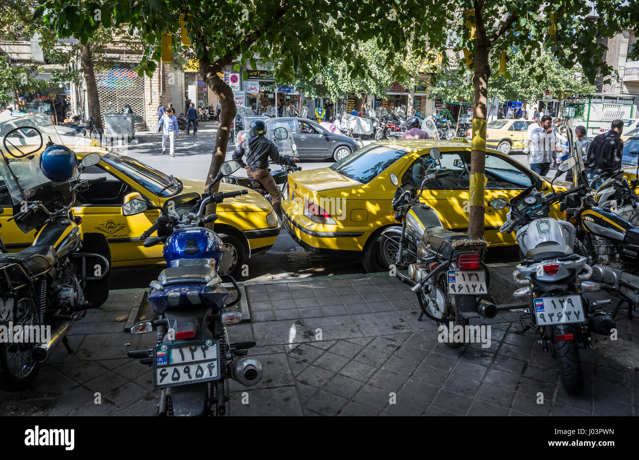 Taxi cabs and scooters on Khayyam Street in Tehran city, capital of Iran and Tehran Province - Stock Image
