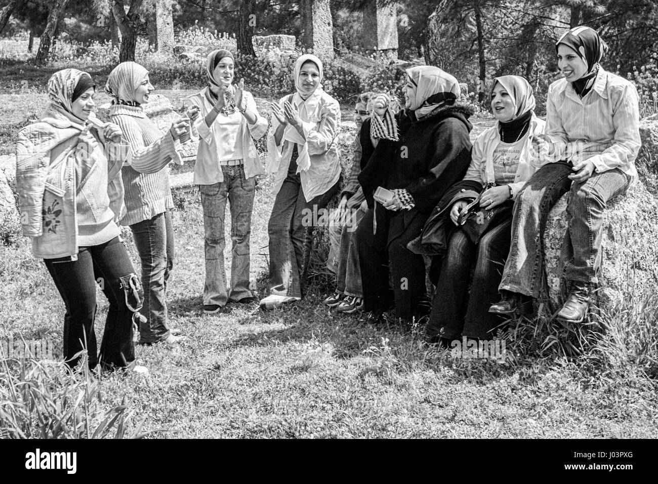 Syrian women singing and clapping as they picnic at the Basilica of St. Simeon in Syria. - Stock Image