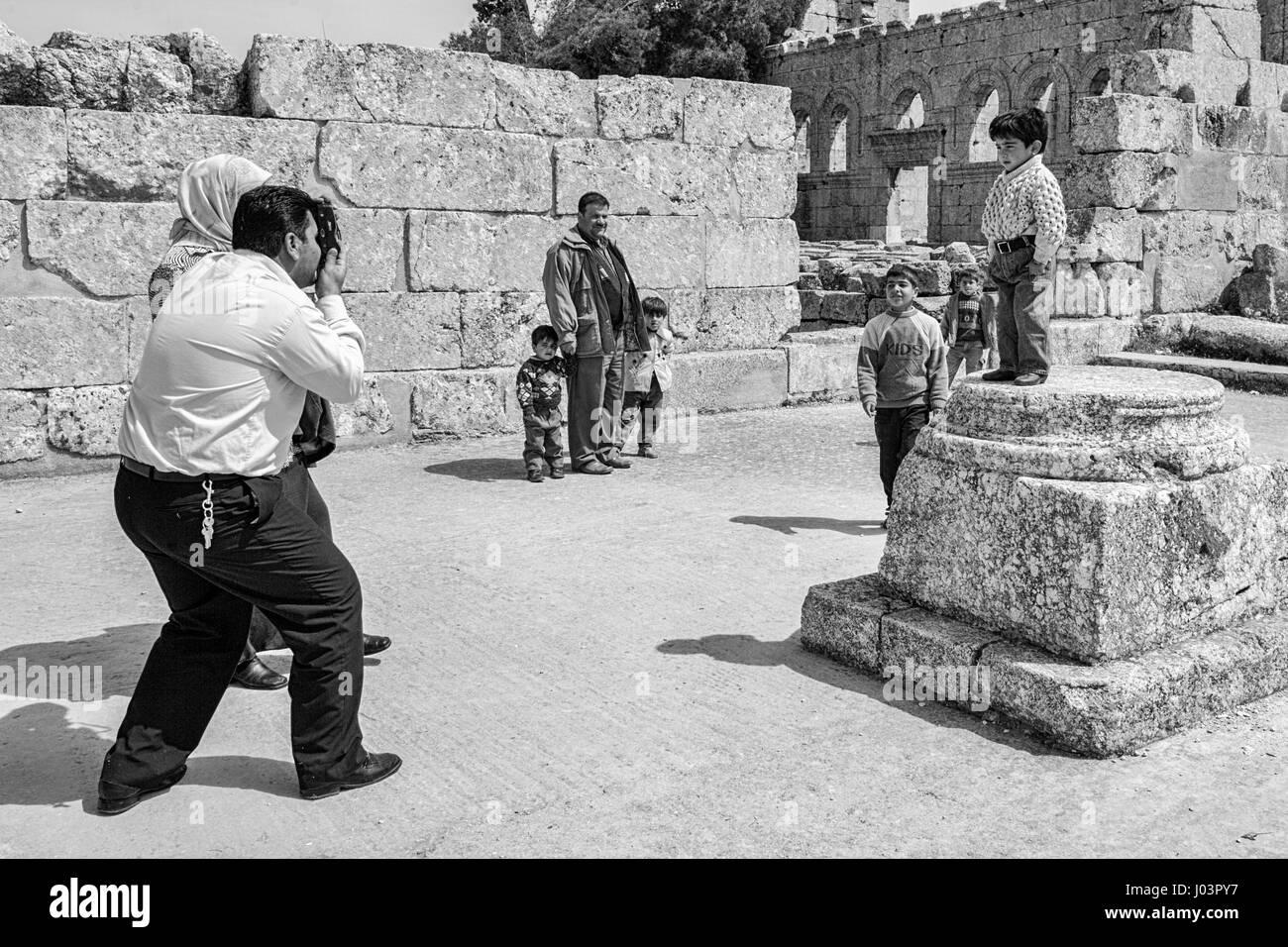 Father photographing his son in the ruins of Qala'at Samaan, Syria. - Stock Image