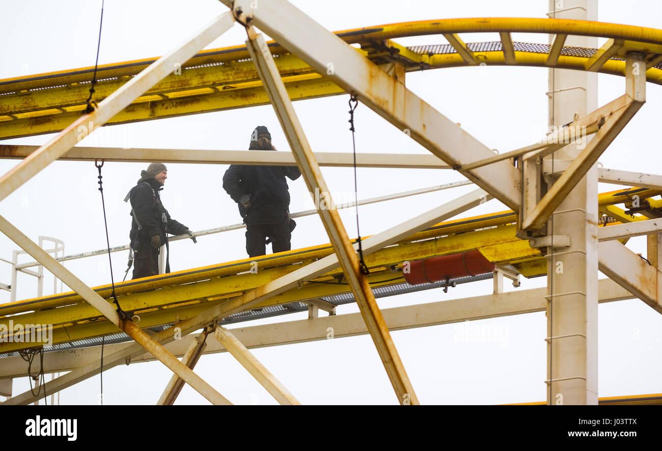 Maintenance men repairing a roller-coaster ride at an amusement park. - Stock Image