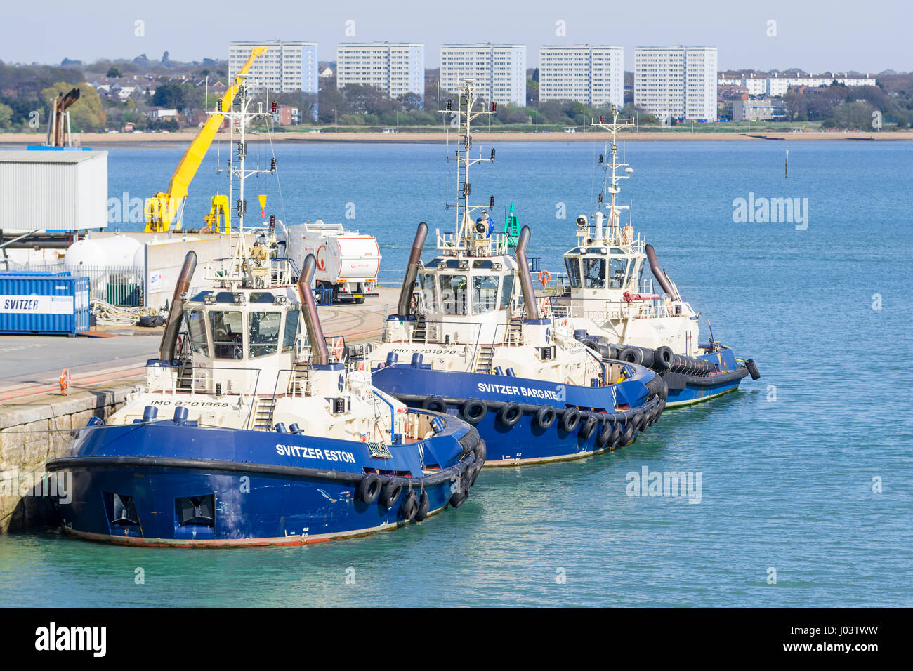 Tug boats at sea. 3 Svitzer tugboats moored in port in the Solent at Southampton, Hampshire, England, UK. Tug names: - Stock Image