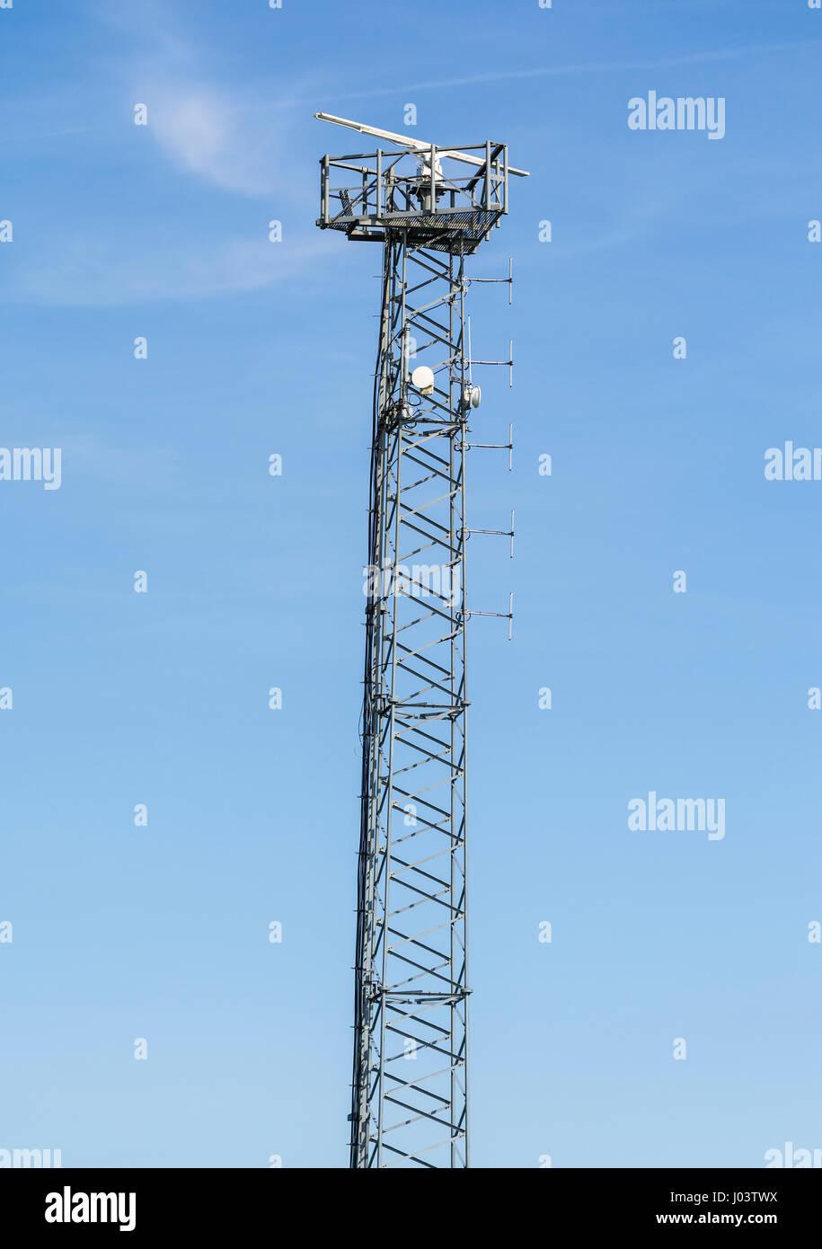 Radar sensor on land on top of a tall metal mast. - Stock Image