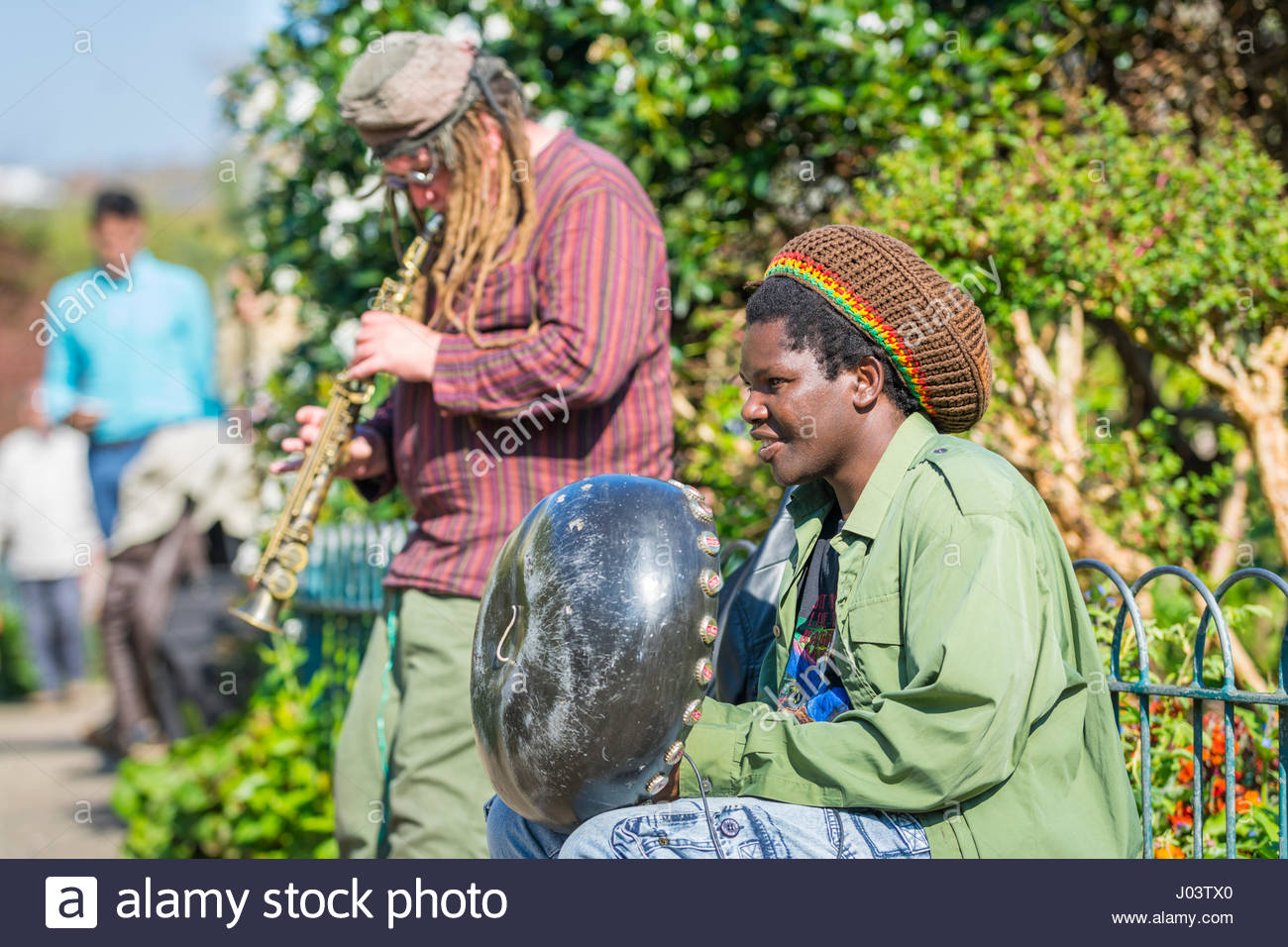 Pair of buskers playing instruments in a park in the UK. - Stock Image